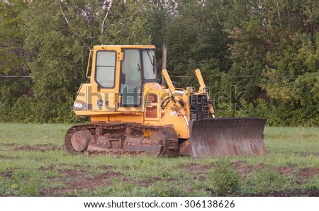 FOX HARBOUR, CANADA - AUGUST 11, 2015: John Deere bulldozer in field. John Deere is an American company manufacturing heavy industrial and lawn care equipment.