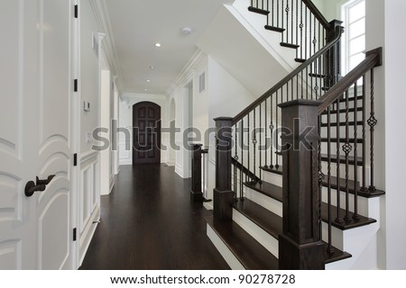 Foyer in new construction home with dark wood staircase - stock photo
