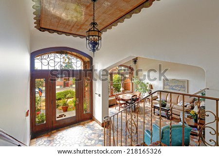 Foyer in old residential building in Downtown, Seattle. Mosaic tile floor, decorated ceiling and wooden entrance door together with wrought iron railings merge a visitor into historic atmosphere - stock photo