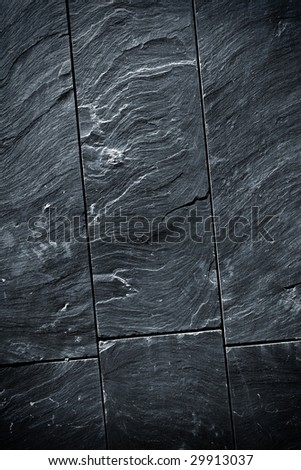 Fraction of a black schist wall with sharp texture - stock photo