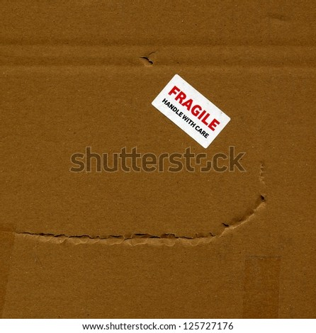 Fragile (handle with care) brown corrugated cardboard packet - stock photo