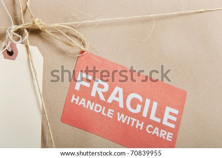 Fragile package wrapped in brown craft paper with label; tag and string on it - stock photo