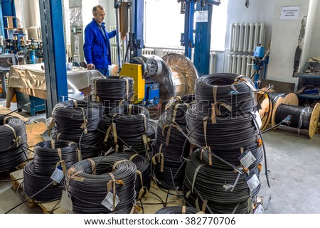 Fragment inside a modern plant producing power electric cable and optical fiber. Interior of modern production line. Finished goods on container cable reels for transportation and sale of consumer