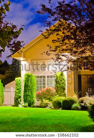 Fragment of a big luxury house with the triple garage doors at dusk, night time. - stock photo