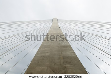 fragment of a cable bridge against  clouds sky background