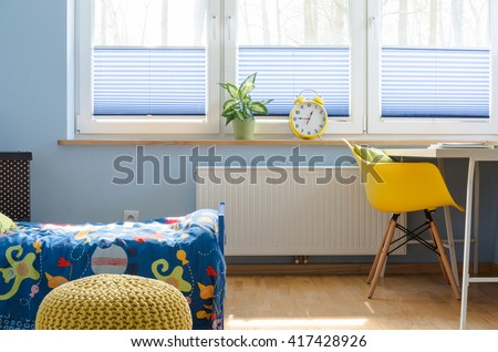 Fragment of a child room with large blinded window, radiator underneath, covered bed and desk with chair beside it - stock photo