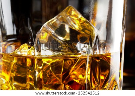 Fragment of a glass of whiskey with ice on a black background - stock photo