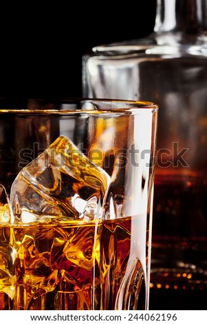 Fragment of a glass of whiskey with ice on a dark background with a carafe - stock photo