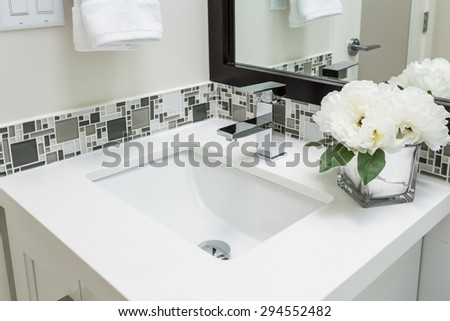 Fragment of a luxury bathroom with flowers and towels. View of a white modern sink. Interior design. - stock photo