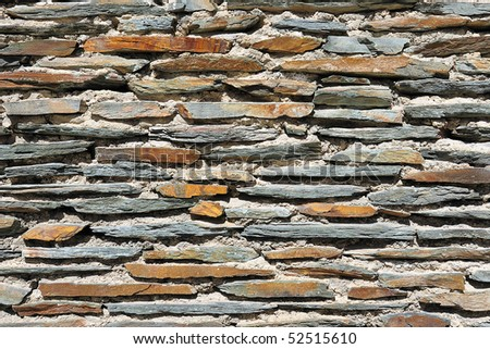 Fragment of a stone wall made of flagstone bricks