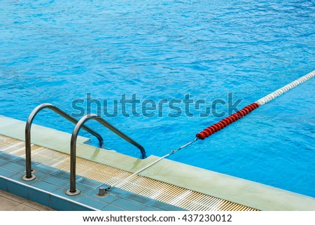 Fragment of a swimming pool with a lane rope and a ladder - stock photo