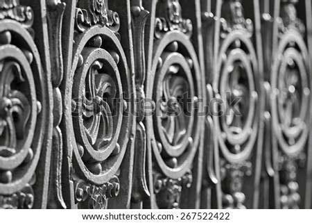 fragment of an ancient pig-iron fence with the abstract forged pattern of gray color - stock photo