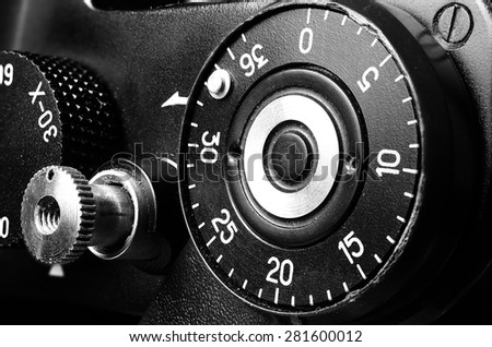 Fragment of an old film camera. Top view of the dial of exposure, the shutter button and the frame counter. Close up view. Macro. Vintage photo. Toning. - stock photo