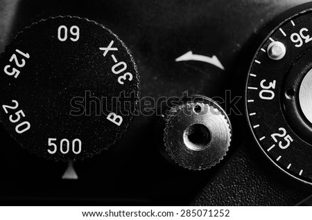 Fragment of an old film camera. Top view of the dial of exposure, the shutter button and the frame counter. Close up view. Macro. Vintage photo. Black and white. - stock photo