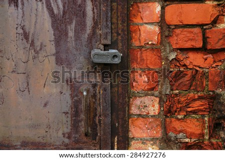 Fragment of an old metal door closed with a lock and of wall from red brick - stock photo