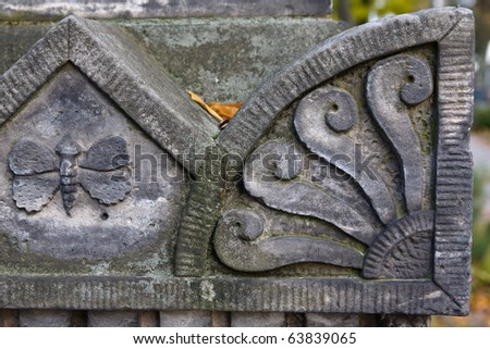 Fragment of an old sculptured gravestone in autumn - stock photo