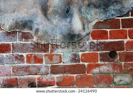 Fragment of ancient brick wall with traces of plaster on it