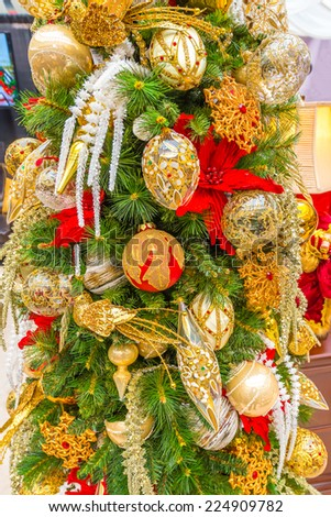 Fragment of beautiful christmas tree decorated and lighted with gifts and ornaments for Christmas and for New Year Eve. - stock photo