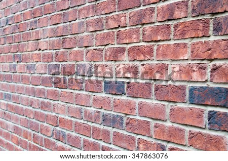 Fragment of brown brick wall with a shallow depth of field, which is photographed at an angle to the plane. Selective focus. - stock photo