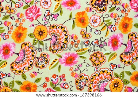 Fragment of colorful retro tapestry textile pattern with handmade floral ornament and flowers as background. - stock photo