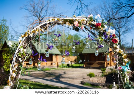 Fragment of creatively decorated wedding arch with lamps and natural flowers outdoors  - stock photo