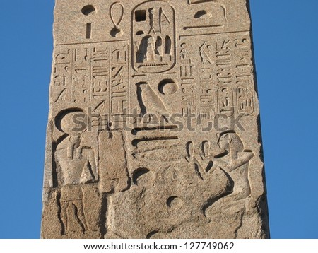 Fragment of Egypt obelisk with carved figures and hieroglyphics on blue sky background