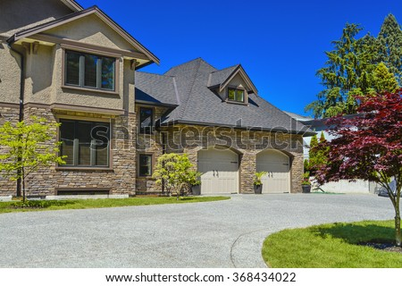 Fragment of luxury house with double garage and concrete driveway in front. Front yard of luxury family house with green lawn and driveway in front on blue sky background - stock photo