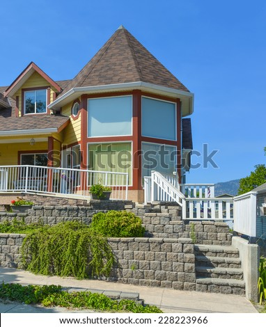 Fragment of luxury residential house with stone stair in front and blue sky background, Canada. - stock photo