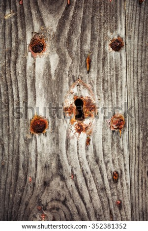 Fragment of old wooden door with rusty keyhole - stock photo