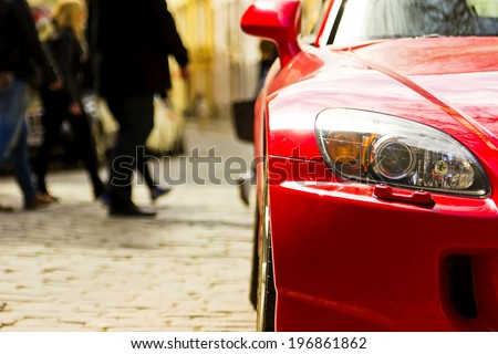 Fragment of red sport car with headlight in sunlight at sunset - stock photo