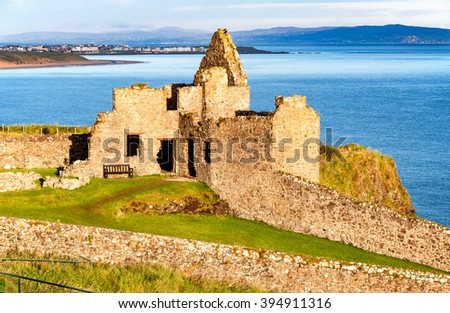 Fragment of ruins of Dunluce castle in County Antrim, Northern Ireland, UK, with the far view of  Portrush resort in the background - stock photo