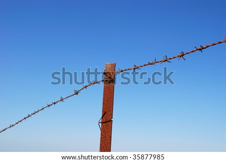 Fragment of rusty barbed wire on blue sky background - stock photo