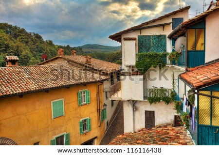 Fragment of small italian town with colorful houses, roofs covered by tiles and small balconies under the autumnal cloudy sky in Barolo, Italy.