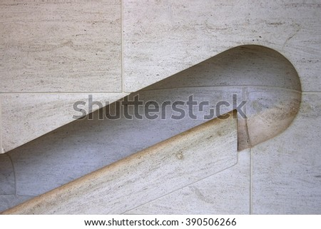Fragment of staircase hall wall with handrail of natural stone. Metaphor of support, trend or progress. Abstract architectural / interior background in sand / light beige color. - stock photo