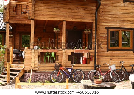 fragment of summer cottage log house with wooden porch window and bicycles - stock photo
