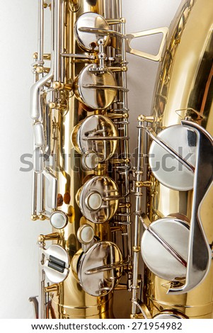 Fragment of Tenor Saxophone on white background. Tenor sax close up. Close up of keys tenor saxophone. Wonderful instrument. For right hand.