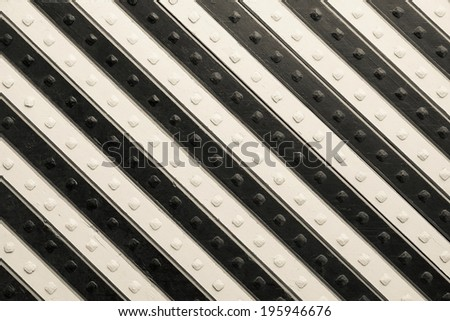 fragment of the ancient riveted panel from the painted wooden boards with black beige slanting striped pattern - stock photo