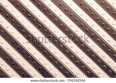 fragment of the ancient riveted panel from the painted wooden boards with brown beige slanting striped pattern - stock photo