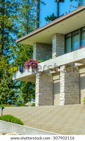 Fragment of the big custom made luxury modern house with nicely paved driveway in the suburbs of Vancouver, Canada. Vertical. - stock photo