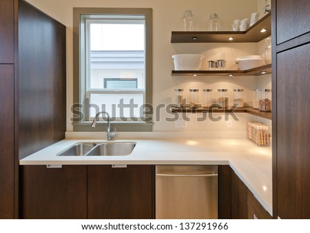 Fragment of the luxury modern kitchen with some shelves with  jars, cans in the corner and window atop of the sink. Interior design. - stock photo