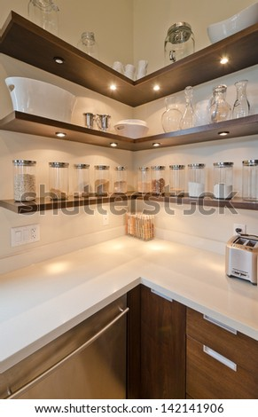Fragment of the luxury modern kitchen with some shelves with jars, cans in the corner. Interior design.