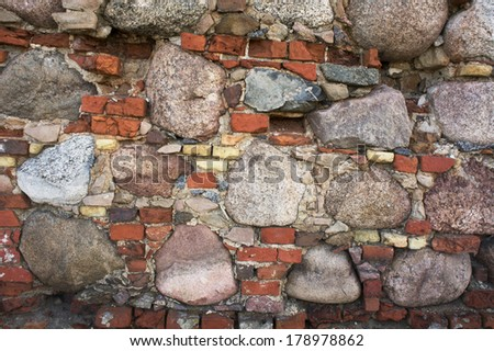 fragment of the old wall of stone and brick - stock photo