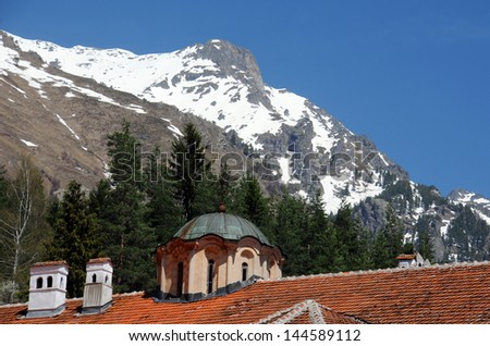 Fragment of the Rila monastery with the snowy top of the Rila mountains in the background - stock photo