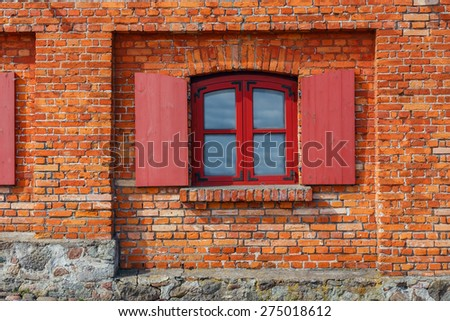 fragment of the wall of red brick with window and shutters