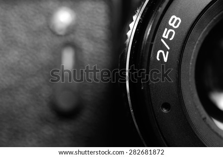 Fragment old film DSLR camera with lens. Lens and camera self-timer button. Front view. Macro. Selective focus. Vintage photo. Black and white. - stock photo