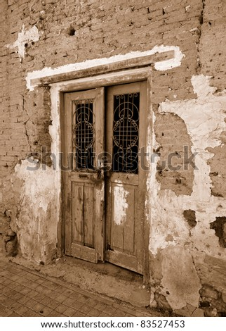 Fragment wall of old abandoned building with cracked rusty door. Sepia - stock photo