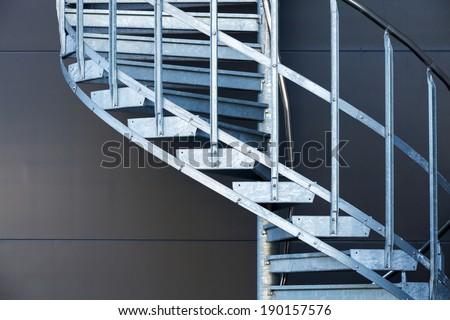 Fragmetn of modern metal spiral staircase above dark gray wall - stock photo
