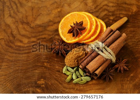 fragrant cinnamon sticks, star anise, cardamom and orange on a wooden background - stock photo