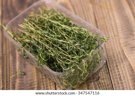 Fragrant eating rosemary pot-herb healthy organic ingredient spiciness with piquant flavour in plastic food box on wooden background studio closeup, horizontal picture  - stock photo