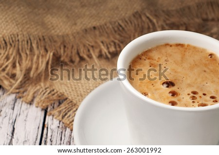 Fragrant, natural coffee in a cup standing on a wooden table - stock photo